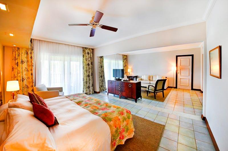 Vista geral do quarto com cama casal grande e televisão posta ao fundo